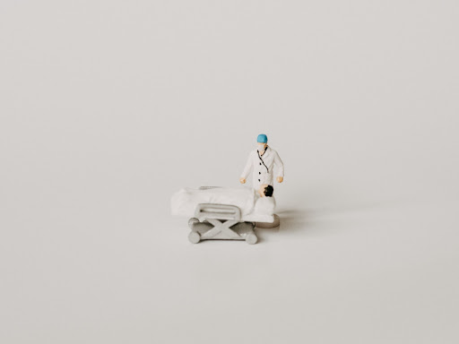 Toy figure of surgeon and patient, centred against a white backdrop
